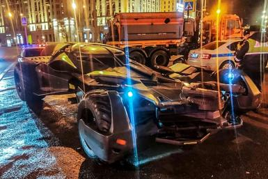 """This handout photo from Russian Interior Ministry taken on February 22, 2020 shows Russian traffic policemen standing next to a vehicle in Moscow that bears a striking resemblance to the """"Batmobile"""""""