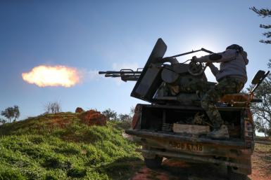 A fighter fires a truck-mounted gun towards Syrian government positions in Saraqeb as the rebels prepare to move on the key northwestern crossroads town