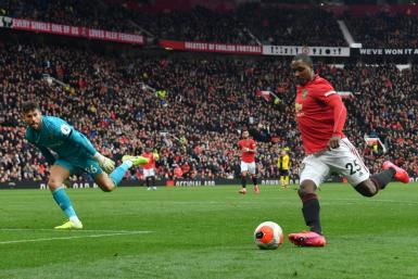 Odion Ighalo has joined Manchester United from China's Shanghai Shenhua on loan (R) rounds Watford's English goalkeeper Ben Foster (L) during the English Premier League football match between Manchester United and Watford at Old Trafford in Manchester,
