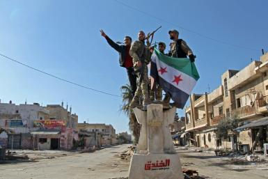 Turkish-backed Syrian rebels celebrate their recapture of the stategic crossroads town of Saraqib in a counterattack that reversed one of the main gains of a government offensive on their last major stronghold