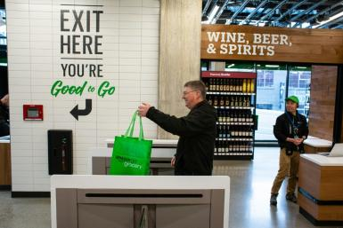 A shopper exits Amazon Go Grocery on February 26, 2020 in Seattle, Washington, the first full-sized retail grocery location that uses the cashier-free model