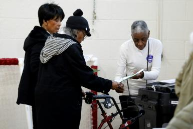 People wait to put their ballots in the tabulation machine at Chrysler Elementary School in Detroit