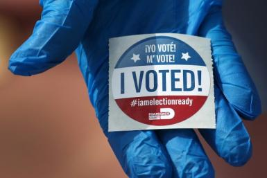 A voter wearing a glove holds an 'I Voted!' sticker after casting her ballot in the Florida primary