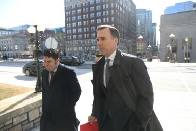 Canada's Finance Minister Bill Morneau (R) arrives at parliament for a news conference to detail emergency funding measures to help Canadians and businesses weather the coronavirus pandemic