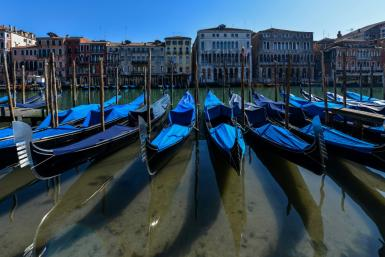 Gondolas sit empty in Venice's Grand Canal with Italy in lockdown to confront the dire impact of new coronavirus which, in one day, killed 475 more people in the country