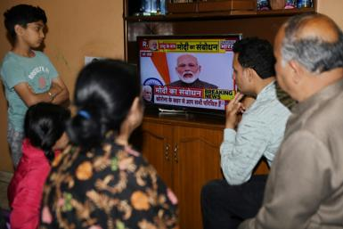 A family watches Prime Minister Modi's address to the nation at their home in Amritsar