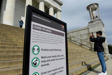 Tourists take pictures near a sign informing about coronavirus safety measures at the Lincoln Memorial on March 27, 2020 in Washington, DC