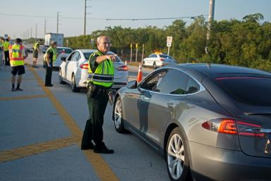 Police man a traffic stop on the route to the Florida Keys, which have been temporarily closed to visitors since March 22 because of the coronavirus crisis