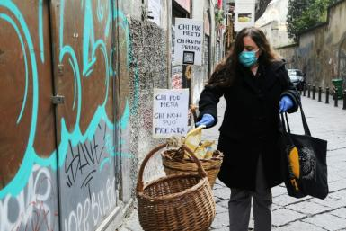 """A woman puts food in a solidarity basket displayed with a note reading, """"Who can put, who cannot take"""" in Naples, as Italy sees evidence it may have made it through the worst of the coronavirus pandemic"""