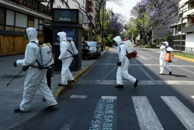 Cleaning workers wearing personal protective equipment disinfect a street in Mexico City amid the COVID-19 outbreak