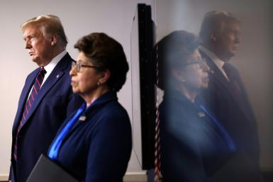 US President Donald Trump stands with the head of the Small Business Administration, Jovita Carranza, during a White House briefing on April 2