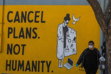 "A man wearing gloves and a face mask walks by a mural reading ""Cancel Plans Not Humanity"" in Los Angeles, California"