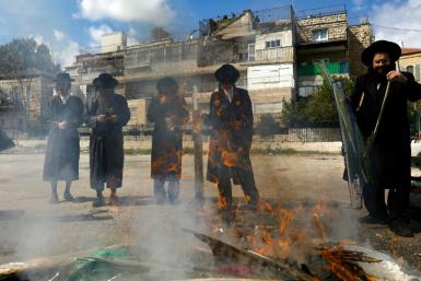 Jewish men burn food with leavening agents ahead of the start of Passover, in the the ultra-Orthodox Mea Shearim neighbourhood of Jerusalem