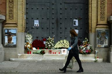 A woman walks past a church in Seville, adorned with flowers and candles left by the faithful after Easter processions were cancelled