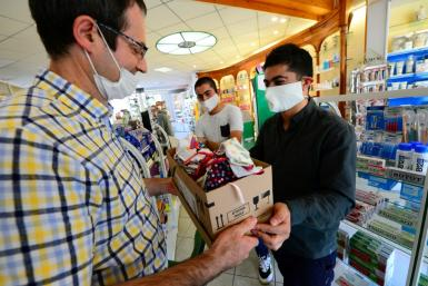 Syrian refugee Mustapha Shikho hands over a box of protective masks to the local pharmacist