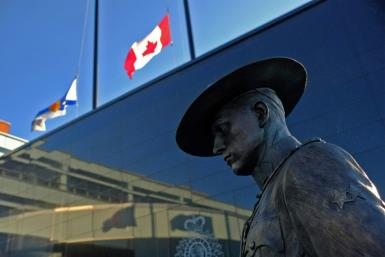 Flags of Nova Scotia and Canada fly at half-staff outside the Nova Scotia Royal Canadian Mounted Police (RCMP) headquarters in Dartmouth, Nova Scotia, after at least 10 people including an RCMP officer were killed in a shooting rampage