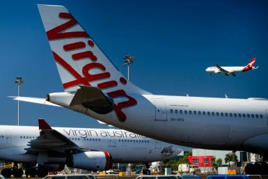 Virgin Australia aircraft are parked on the tarmac at Brisbane International airport while a plane from Qantas, the only other Australian full-service carrier, flies in the background