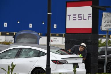 A Tesla employee cleans a car outside a Tesla showroom in Burbank, California, March 24, 2020