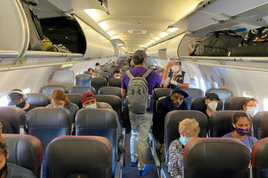 Passengers, all but one wearing masks, board an American Airlines flight from New York to Charlotte, North Carolina, on May 3, 2020