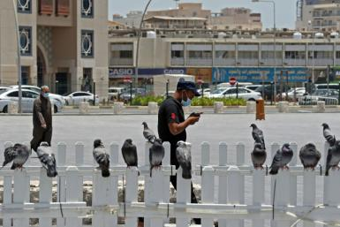 A masked man checks his phone in Qatar where residents and citizens have been required by law to install a coronavirus contact tracing app on their handsets since Friday