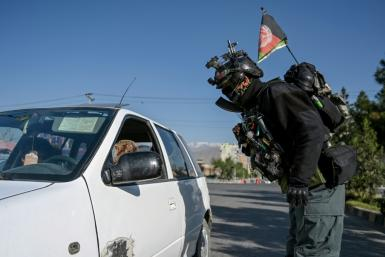 A motorist is checked by security at a checkpoint in the Afghan capital at the start of the Eid al-Fitr holiday