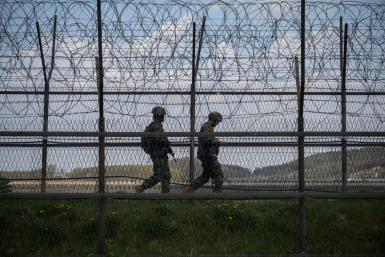 South Korean soldiers patrolling along a barbed wire fence at the Demilitarized Zone with North Korea