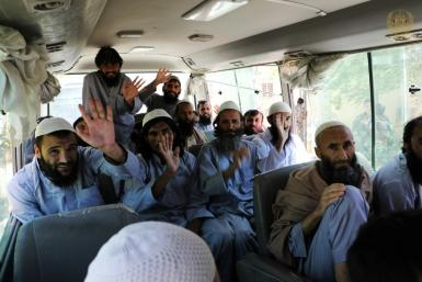 Taliban fighters wave on a bus after being released from prison in Bagram in a handout photograph released Afghanistan's National Security Council