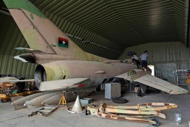Fighters loyal to Libya's UN-recognised Government of National Accord (GNA) climb over a partially disassembled MiG 23 aircraft, after seizing Al-Watiya airbase southwest of the capital Tripoli, on May 18, 2020.