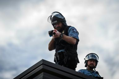 Two police officers stand on the roof of the Third Police Precinct holding a projectile launcher during a demonstration against the death of George Floyd, in Minneapolis, Minnesota on May 27, 2020