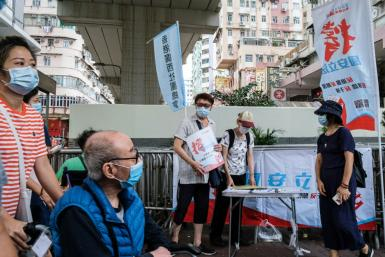People stand at a booth where passersby can give their signatures in support of a new security law in Hong Kong