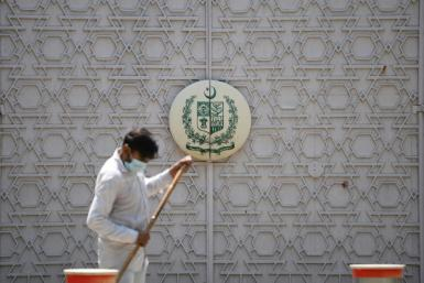 A man sweeps in front of the main gate of the Pakistan High Commission in New Delhi