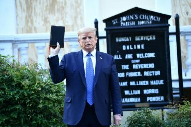 US President Donald Trump holds up a bible in front of St John's Episcopal church after walking across Lafayette Park from the White House in Washington, DC on June 1, 2020