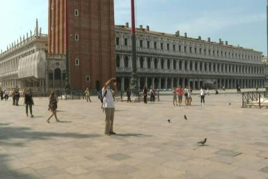 People walk around St Mark's Square in Venice, Italy, with some taking pictures of the famous sites as the country reopens to tourists from Europe after a months-long coronavirus lockdown