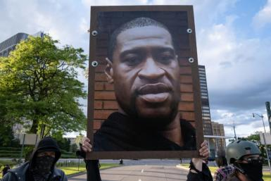 Protesters hold a picture of George Floyd in Detroit, Michigan on May 30, 2020