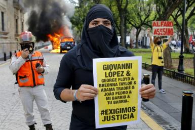 The arrests followed riots in Guadalajara after protesters had gathered to demand justice over Giovanni Lopez's death; a demonstrator holds a banner during a protest in Guadlalajara, Jalisco