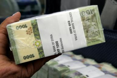 A bank worker in Damascus holds up a bundle of Syrian 1,000-pound bank notes