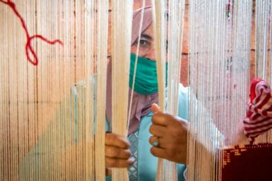 A Moroccan rug weaver peeks from behind carpet thread at a workshop in the city of Sale, north of the capital Rabat