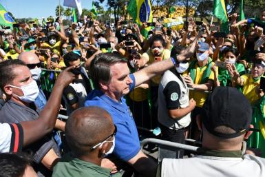 Brazilian President Jair Bolsonaro (C) has opposed lockdown measures
