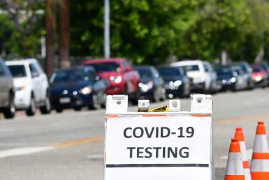 Drivers in their vehicles wait in a long line at a coronavirus testing site in Los Angeles, California