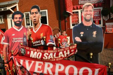 Liverpool fan Emily Farley sits outside her home, decorated with Liverpool banners and cut-outs, as she waits for the result of the match between Chelsea and Manchester City