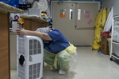 A medical worker rests in front of a fan in the COVID-19 intensive care unit at United Memorial Medical Center in Houston, Texas