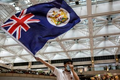A protester waves the former British colonial Hong Kong flag at arally in a shopping mall. A new Chinese security law imposed on the city is causing fresh tension between London and Beijing