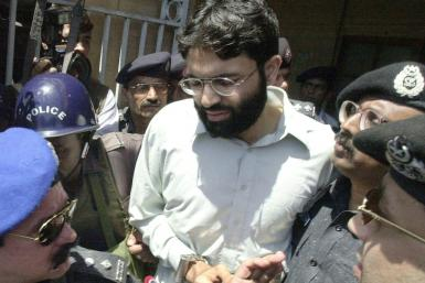 In this photo taken on March 29, 2002, Pakistani police surround handcuffed Omar Sheikh as he comes out of a court in Pakistan's port city of Karachi