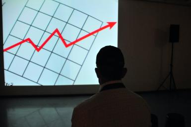 Man wearing white top at projector graph screen
