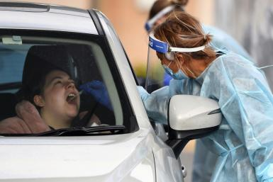 A coronavirus tester takes a swab sample at a drive-through testing station in Melbourne