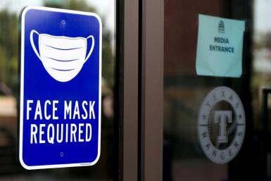 A face mask sign on the door is the first thing visitors to the Texas Rangers training facility in Dallas see as they enter Globe Life Field.