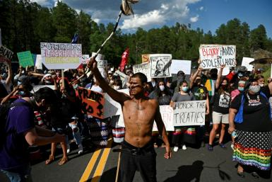 Activists and members of different tribes block a road near Mount Rushmore as they protest the US government in Keystone, South Dakota on July 3, 2020, ahead of a visit by President Donald Trump