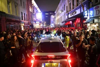 A car tries to drive along a street filled with people drinking in the Soho area of London