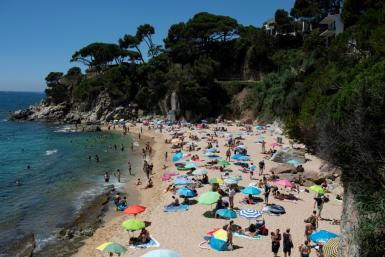 People enjoy a day out at the beach in Platja D'Aro near Girona -- Spaniards endured one of the world's toughest lockdowns for three months from March 2020