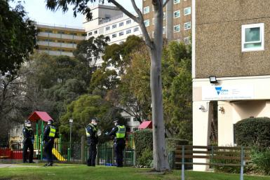 Police stand guard outside a public housing estate locked down in Melbourne due to a spike in coronavirus cases